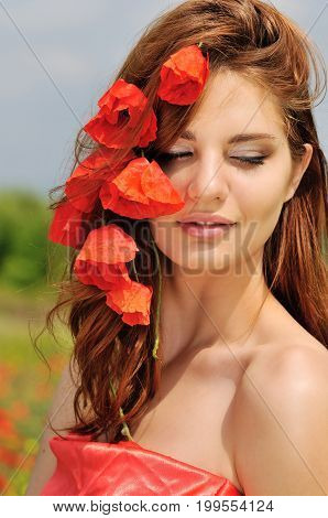 portrait of a beautiful lady with poppies in hair in a poppy field