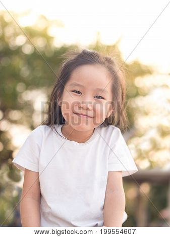 happy Asian child on a seesaw in sunset light wearing white t shirt