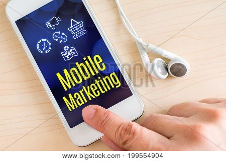 Hand touch smart phone and ear phone with Mobile marketing word on wood table Digital Marketing concept