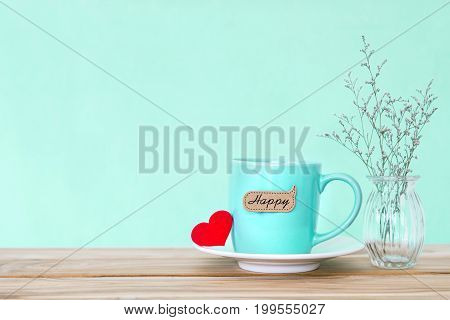 Coffee cup mug with red heart shapeand happy word tag on wooden table Romance and love valentines day background concept
