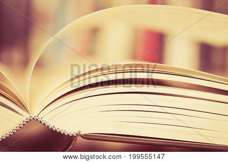 Close up opened book page with blurry bookshelf background for education and bublication concept extremely DOF with vintage retro color tone