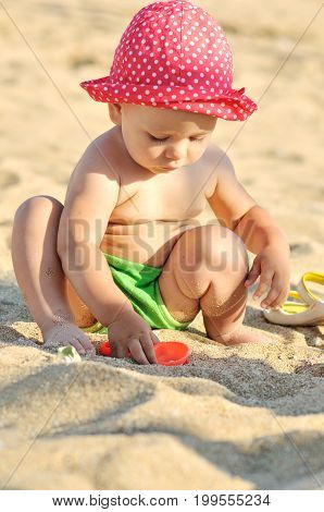Baby With Toys On The Beach