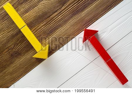 Two arrows pointing in opposite directions. Two wooden arrows red and yellow.