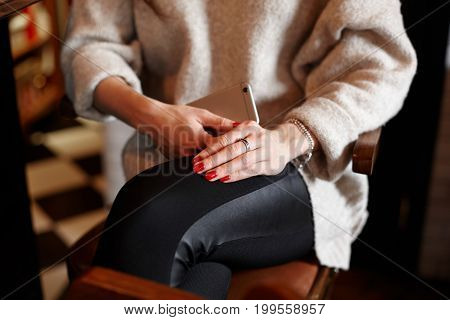 Cropped shot of stylish unrecognizable young woman in trousers and sweater sitting on chair at restaurant using generic mobile phone. Close up view of female hands with red nails holding gadget