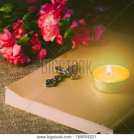Close Up Image Of Metal Cross God And Candlelight On Classic Paper Book With Pink Carnation Flawer B