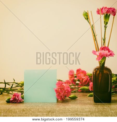 Bright Pink Carnations Flower In The Japanese Glass Vase On Table And Blank Blue Card . Vintge Image