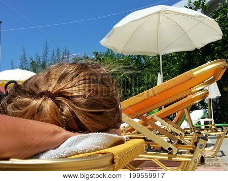 View on a beautiful relaxed Women on the Poolside. Close-up of a sleeping woman in Summer. Relaxed Woman on a Sunbed