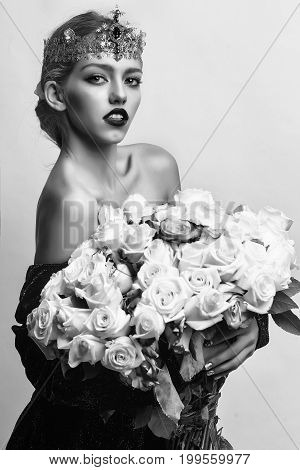 girl with luxury crown with diamond and gem has bare shoulders hold rose bouquet black and white
