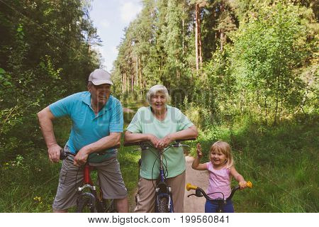 active seniors with granddaughter riding bikes in summer nature