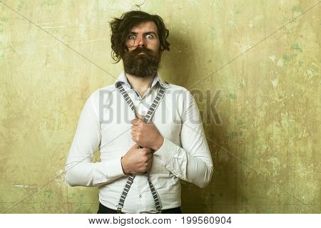 Hipster in shirt and suspenders. Man with long beard and mustache on scared face. Fashion model with stylish hair. Guy or businessman at textured wall. Business fashion and beauty.