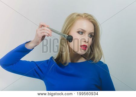 Girl With Red Lips Applying Makeup On Face With Brush