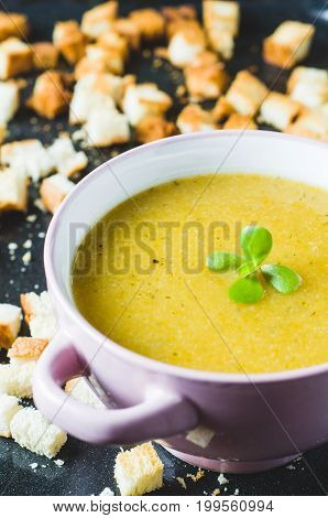 Vegetable Cream Soup In A Pink Bowl And Croutons On A Dark Background