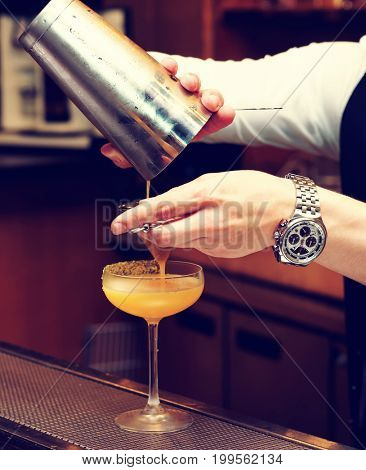 Bartender is pouring cocktail from shaker into a glass, toned image