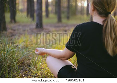 Middle Aged Woman Sitting In Lotus Position In Forest. Her Eyes Are Closed. Middle-aged Woman In Her