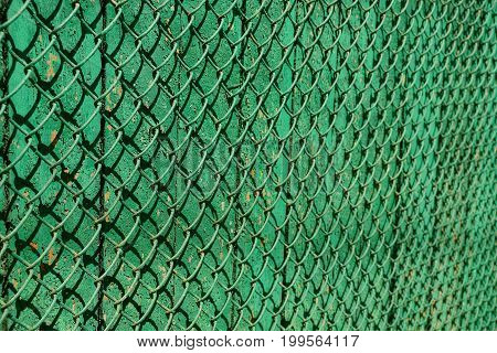 A fragment of a wooden fence and an iron grid of green color