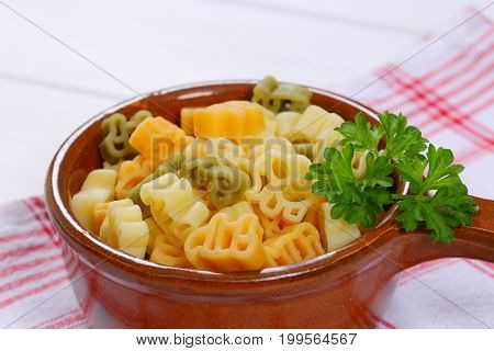 saucepan of cooked colored pasta on checkered dishtowel - close up