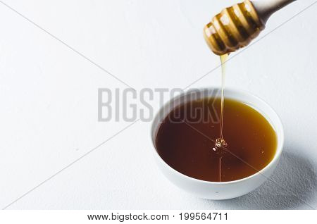 Fresh Honey In A White Cup On A White Concrete Background