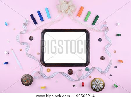 Background with stylish sewing tools and accessories on trendy pink background.