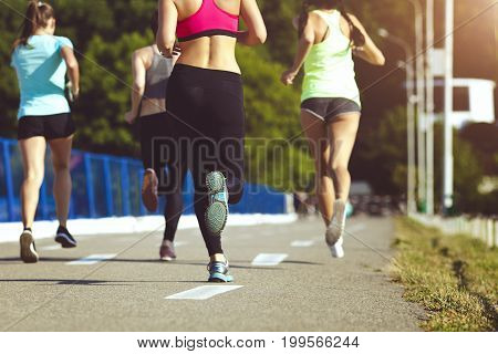 Healthy sports people trail running living an active life. Happy lifestyle athletes training cardio together in summer outdoors. Group woman runs on the sports track back view.