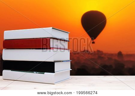 stack book on desk no labels blank spine with blurred view of silhouette of balloon at sunrise in the morning over Bagan in Myanmar education back to school history landscape nature concept