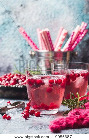 Refreshing drink with cranberries, ice and rosemary on gray stone background. Christmas cocktail