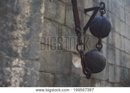 Details of the ancient lifting post in the fortress: metal balls counterbalances fixed in a stone wall. Medieval defense fortifications. Kotor fortress in Montenegro.