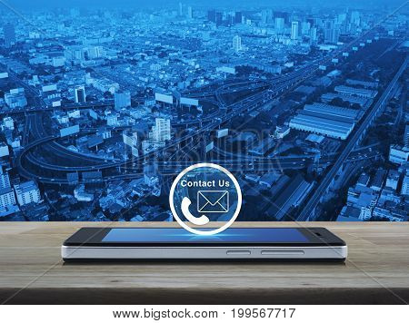 Telephone and mail icon button on modern smart phone screen on wooden table over city tower street and expressway Contact us concept