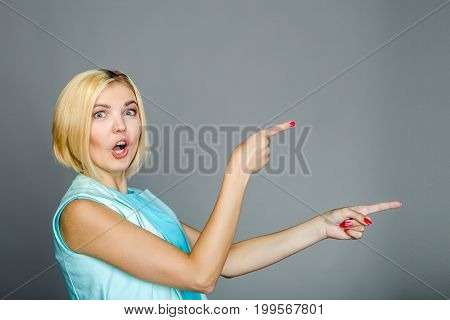 Beautiful girl points with fingers on blank space for text at gray background
