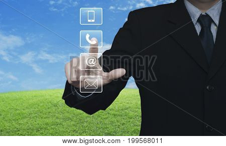Businessman pressing telephone mobile phone at and email buttons over green grass field with blue sky Customer support concept