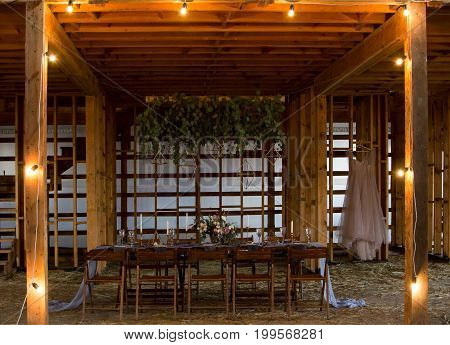 Wedding and decor. Wedding party.Candles and bouquet. Vintage Style. Setout by wedding banquet in a wooden barn.