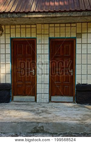 Two closed wooden doors on the wall of the apartment house