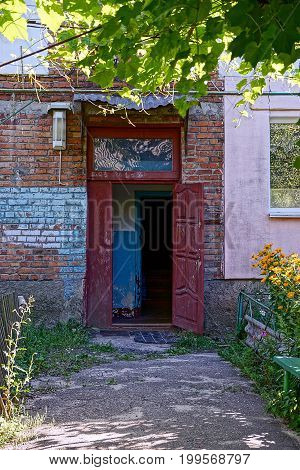 Open door to the entrance of an apartment house in the yard