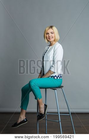 Beautiful model sitting on bar chair in studio