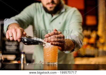 Bartender pours ice into an orange cocktail no face