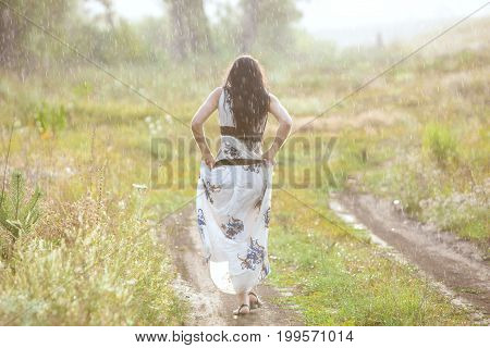 Woman is walking along a rural road during the rain she is completely wet.