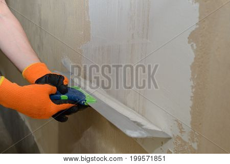 Plastering of the plastered wall with white plaster filler