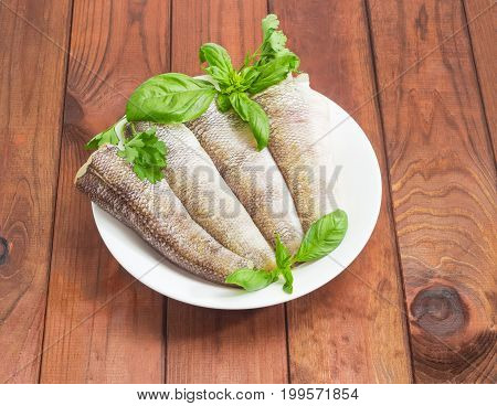 Uncooked carcasses of the notothenia fish without of a heads and tails and with peeled scales and prepared for cooking twigs of basil and parsley on the white dish on a dark wooden surface