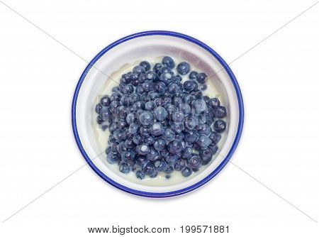 Top view of the dessert made of the fresh wild bilberries and sweetened condensed milk in the blue bowl on a white background