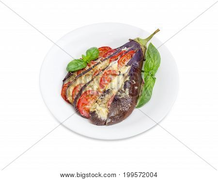 Baked eggplant stuffed with vegetables and cheese decorated with basil leaves on white dish on a white background