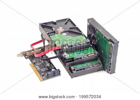 Several SATA hard disk drives disk array controller card and interface cables on a white background