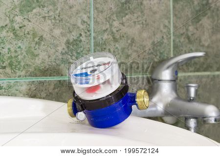 Not connected residential water meter for consumption measuring of a cold water on a wash basin on background of a handle mixer tap and wall with green tiles