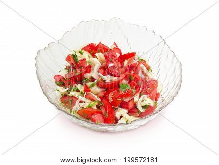 Vegetable salad of a fresh sliced tomatoes white bell pepper onion and potherb in a glass salad bowl on a white background
