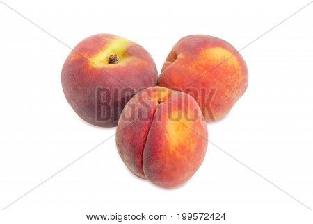 Three ripe fresh peaches on a white background