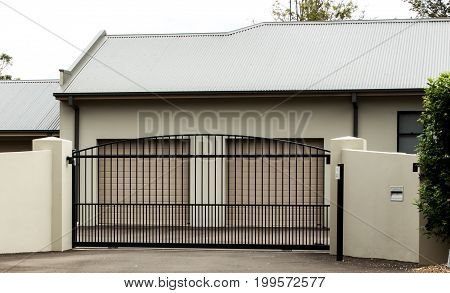 Metal driveway entrance gates set in brick fence with double car garage