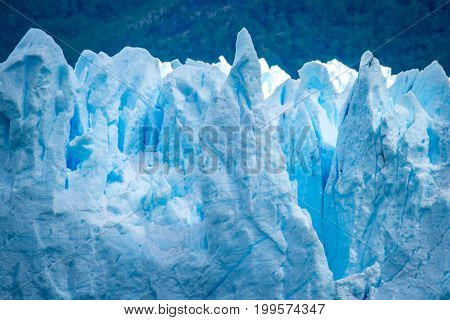 Beautiful view of the surface of a blue glacier. The background is blurred. Uneven surface of the glacier in the sun. The rays of the sun fall on the snow cover of the glaciers.