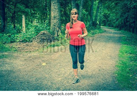 Young attractive woman running in park - retro style