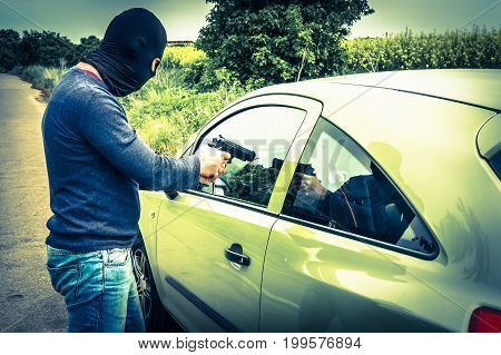 Male thief or terrorist is pointing a pistol on the driver he trying to steal a car - retro style