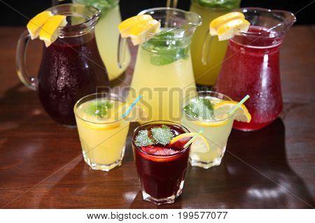 Quenching thirst and refreshing drinks. Cold lemonades. Lemonade. Morse. Berry Lemonade. Summer fruit drinks in glass jugs. Lemonade. Morse. Compote.
