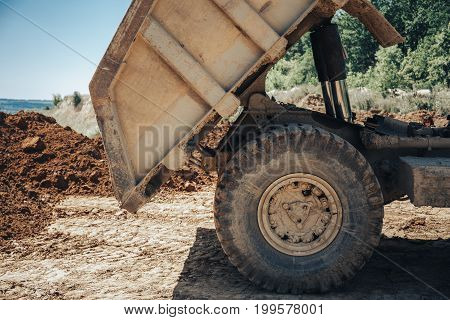 Close-up of the body of a large industrial truck, process of unload, toned