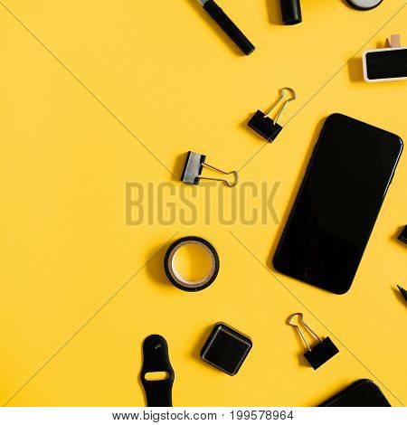 Flat lay home office desk. Workspace with laptop male accessories: diary watch mobile phone on yellow background. Top view modern concept background.